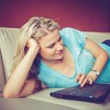 A rapariga bonita está encontrando-se em um sofá e está falando-se através do portátil Imagem de Stock Royalty Free