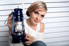 A rapariga bonita guardara uma lâmpada de petróleo Fotografia de Stock Royalty Free