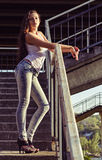 A rapariga bonita na camisa e nas calças de brim está em escadas no tempo do por do sol Imagem de Stock Royalty Free