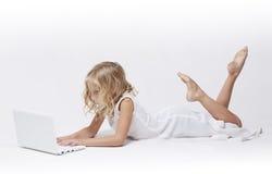 A rapariga bonita no branco, opera seu portátil Imagens de Stock