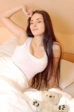 Rapariga bonita que acorda na cama Imagem de Stock