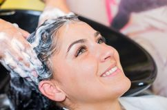 Rapariga bonita que aprecia o cabelo que lava no salão de beleza do hairdressing Imagens de Stock Royalty Free