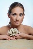 Rapariga bonita que encontra-se na areia com corais imagem de stock royalty free
