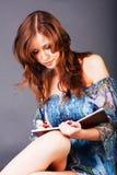 Rapariga bonita que escreveu em um caderno fotografia de stock royalty free
