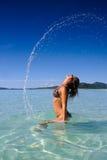 Rapariga bonita que passa rapidamente o cabelo na água Fotos de Stock