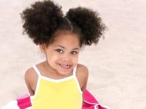 Rapariga bonita que senta-se na toalha de praia na areia Imagens de Stock Royalty Free