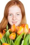 A rapariga bonito está prendendo um grupo dos tulips Foto de Stock