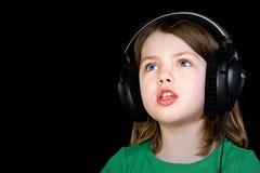 Rapariga bonito que canta com auscultadores Fotos de Stock Royalty Free