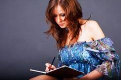 Rapariga Charming que escreveu em um caderno Foto de Stock