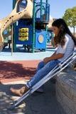 Rapariga com as muletas no campo de jogos Fotos de Stock Royalty Free