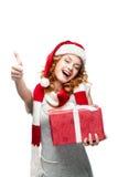 Rapariga com o presente vermelho que mostra o thumbs-up Foto de Stock Royalty Free