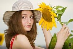 Rapariga com um girassol Fotografia de Stock Royalty Free