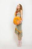 Rapariga com uma abóbora amarela Imagens de Stock