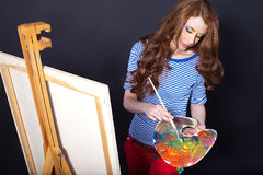 A rapariga com uma paleta e uma escova pinta um pictu Imagens de Stock Royalty Free