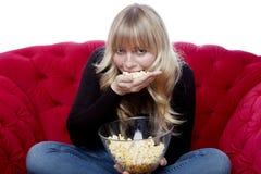 A rapariga come uma mão da pipoca no sofá vermelho imagem de stock