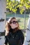 A rapariga custa perto de uma árvore Fotografia de Stock Royalty Free