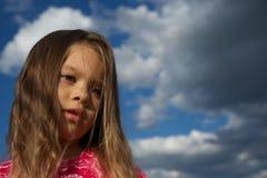 Rapariga de encontro ao céu nebuloso Imagem de Stock