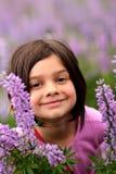 Rapariga de sorriso na correcção de programa de flores selvagens Imagem de Stock Royalty Free