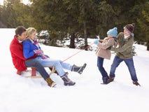 Rapariga e menino que puxam pais através da neve sobre Imagem de Stock