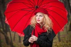 Rapariga elegante bonita com guarda-chuva vermelho, o tampão vermelho e o lenço vermelho no parque Fotos de Stock