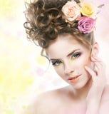 Rapariga encantadora com as flores que tocam na face fotografia de stock