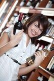 A rapariga escolhe o vinho na loja imagem de stock royalty free