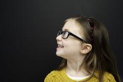 A rapariga esperta estêve o infront de um quadro-negro Imagem de Stock
