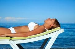 A rapariga está tomando um banho do sol Imagem de Stock Royalty Free