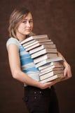 A rapariga está prendendo uma pilha dos livros Fotografia de Stock Royalty Free