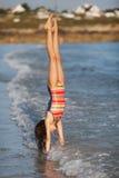 A rapariga faz um handstand na ressaca Fotos de Stock Royalty Free