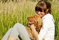 Rapariga feliz que abraça seu cão na GR verde Fotografia de Stock