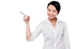 Rapariga feliz que aponta na área de espaço da cópia Foto de Stock