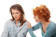 Rapariga incomodada consolada por seu amigo imagem de stock