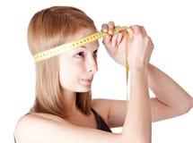 A rapariga mede uma cabeça Imagem de Stock