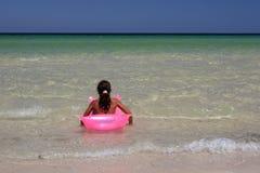 Rapariga na ar-cama cor-de-rosa dentro fotografia de stock