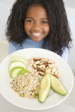 Rapariga na cozinha que come a fruta do arroz e as porcas s Foto de Stock