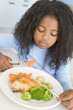 Rapariga na cozinha que come a galinha e o vegetal Foto de Stock Royalty Free