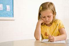 Rapariga na escrita da sala de aula no papel imagens de stock royalty free