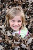 Rapariga na pilha da folha Fotografia de Stock Royalty Free