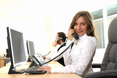 A rapariga no escritório no local de trabalho faz o atendimento Imagens de Stock