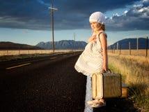 Rapariga no lado da estrada com malas de viagem Fotos de Stock Royalty Free