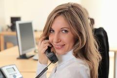 A rapariga no local de trabalho faz o atendimento Foto de Stock