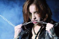 Rapariga no revestimento de couro com a corrente nas mãos Fotografia de Stock Royalty Free
