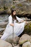 A rapariga no vestido branco com dois entregou a espada foto de stock