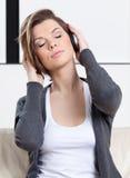A rapariga nos auscultadores escuta a música Imagens de Stock Royalty Free