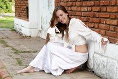 A rapariga perto de uma parede de tijolo Fotos de Stock