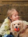 Rapariga que abraça um cão pequeno com esfera Fotografia de Stock Royalty Free
