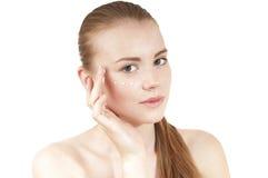 Rapariga que aplica o creme do creme hidratante em sua cara. imagem de stock royalty free