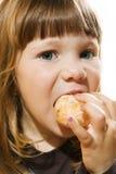 Rapariga que come uma filhós Fotografia de Stock Royalty Free