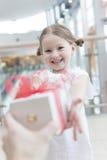 Rapariga que dá um presente Fotos de Stock Royalty Free